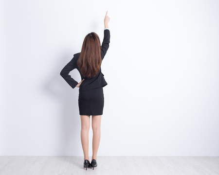 gift behind back: Back view of business woman pointing white wall background, great for your design or text, asian