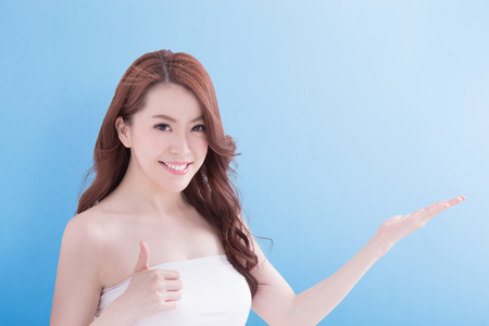 Beauty woman with charming smile and show some to you with health skin and hair isolated on blue background, asian beauty Stock Photo