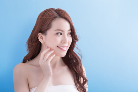 skin care woman: beauty woman smile and look some where happily with isolated blue background, asian