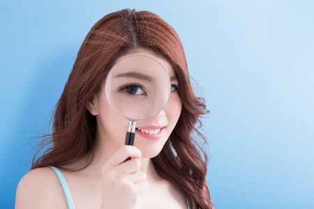 beauty woman take magnifying smile to you with blue background, asian Stock Photo