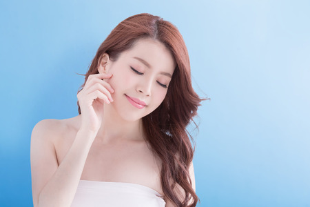 Beauty woman relax closed eye with charming smile with health skin and hair isolated on blue background, asian beauty