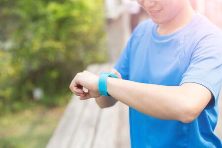 greengrass: man wear wearable smart watch and smiel with green background, asian Stock Photo