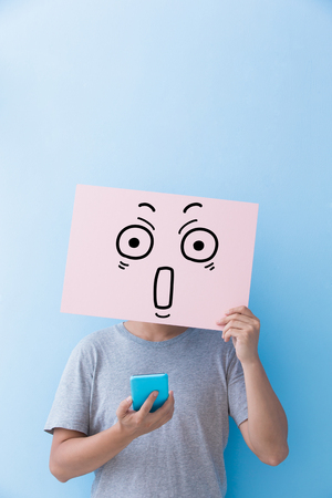 surprise face: man holding surprise expression billboard and take phone isolated on blue background Stock Photo