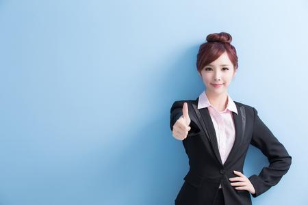비즈니스 여자는 당신에 게 미소이며 엄지 손가락 파란색 배경에 고립 된 아시아 스톡 콘텐츠