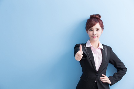 business woman is smile to you and thumbs up isolated on blue background, asian