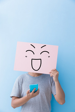 billboard background: man holding happy expression billboard and take phone isolated on blue background Stock Photo