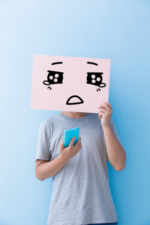 man on cell phone: man holding cry expression billboard and take phone isolated on blue background Stock Photo