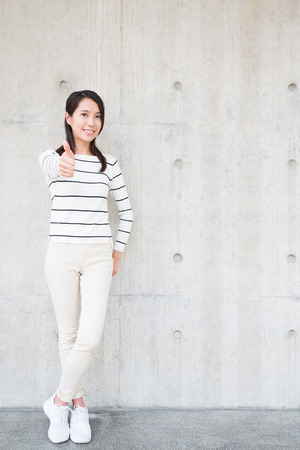 beauty woman smile and thumb up with white wall, asian