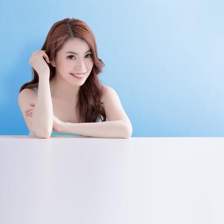 美容皮膚医療女性青い背景の白いテーブルの上に横たわるアジア
