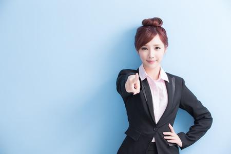 비즈니스 여자는 미소이며 파란색 배경에 고립 된 당신을 가리키는, 아시아