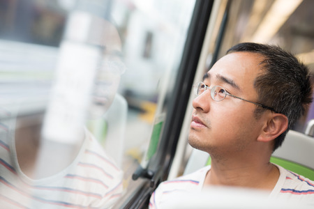man looking out: man looking out the window and take the subway in Hong Kong Stock Photo