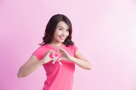 Happy Woman with pink ribbon and show love heart gesture, great for prevention breast cancer concept
