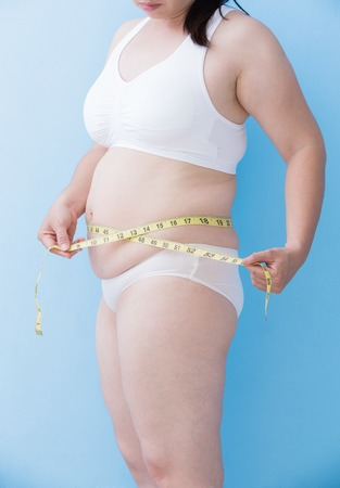 unhealth: Fat overweight woman take waist ruler amount with blue background, asian Stock Photo