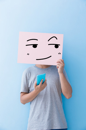 somewhere: man holding look somewhere and smile expression billboard and take phone isolated on blue background Stock Photo
