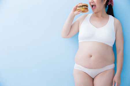 Fat overweight woman hold hamburger with blue background, asian Stock Photo