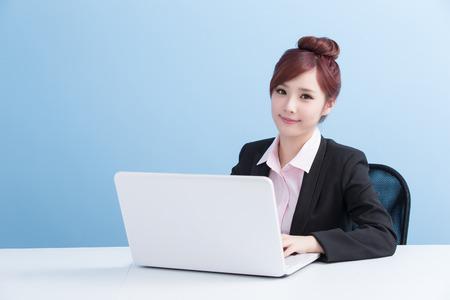 ビジネスの女性の分離の青い背景を持つコンピューターを使用してください。