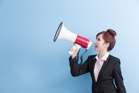 business woman take microphone happily with isolated on blue background Foto de archivo