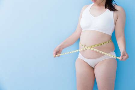 Fat overweight woman take waist ruler amount with blue background, asian Imagens