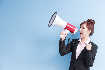 business woman take microphone happily and show fist with isolated on blue background Stock Photo