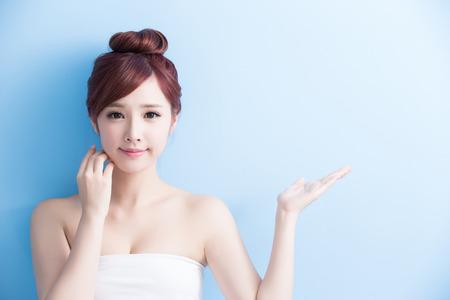 美容皮膚のケア女性魅力的な笑顔と、健康肌と髪が青色の背景、アジアン ビューティーに分離された何かを示さなければ