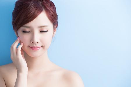 Mujer de belleza cuidado de la piel relaje los ojos cerrados aislados en bluebackground, asiático Foto de archivo - 63605460