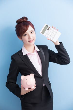 calculator chinese: business woman take pink piggy bank and calculator smile to you with isolated on blue background