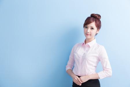 ビジネス女性がほほえみをあなたに分離の青い背景を持つアジアです。