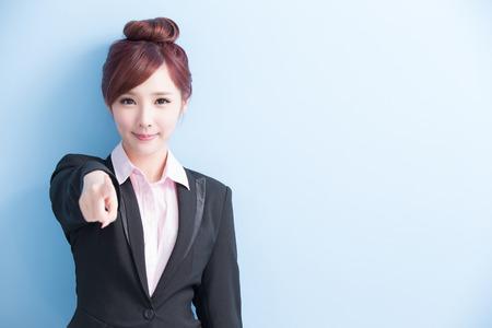 la donna di affari è sorriso e che indica voi isolato su fondo blu, asiatico