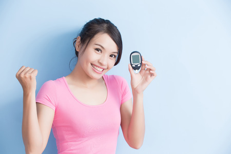 Woman holding a blood glucose meter to prevention diabetes isolated on blue background, asian Stock Photo