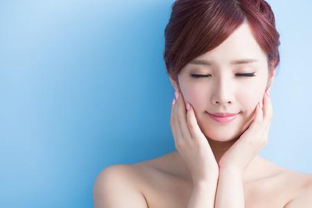 boca cerrada: mujer de belleza cuidado de la piel relaje los ojos cerrados aislados en bluebackground, asiático