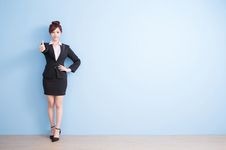 cross arms: business woman is smile to you and thumbs up with blue background, asian