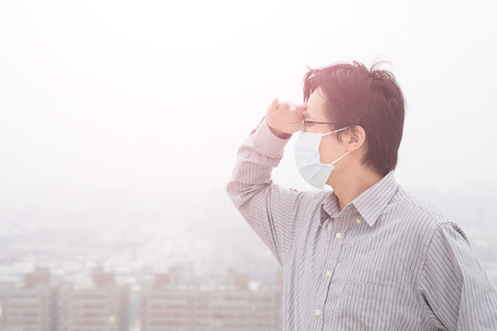 somewhere: man wear masks and look somewhere with air pollution, asian Stock Photo