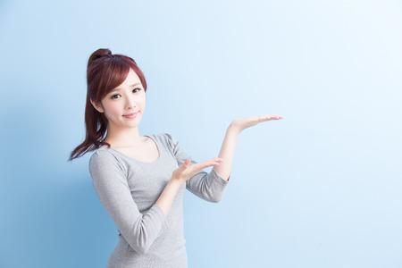 schoonheid meisje student iets laten zien en lach naar je met geïsoleerde op blauwe achtergrond, Aziatische Stockfoto