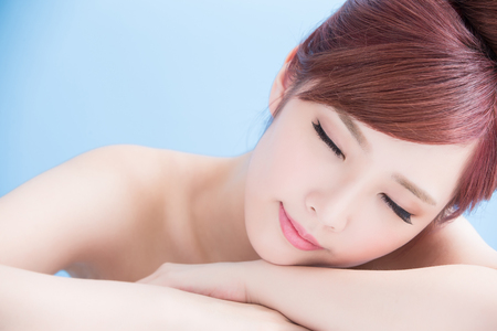 blue face: Charming woman face Smile enjoy spa and massage while lying isolated on blue background, asian girl