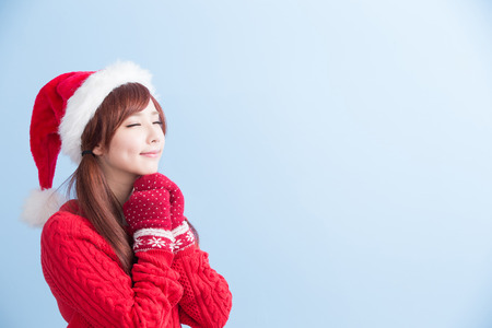 winter fashion: christmas beauty girl make a wish with red hat and cloth isolated on blue background, asian Stock Photo