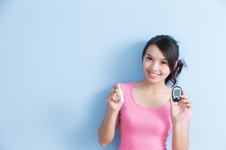 Woman holding a blood glucose meter and inject to prevention diabetes isolated on blue background, asian Zdjęcie Seryjne