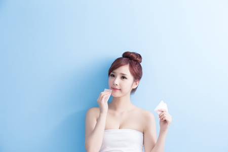 beauty skin care woman smile and make up on her face isolated on blue background, asian 版權商用圖片