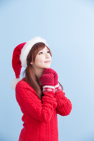 christmas beauty girl make a wish with red hat and cloth isolated on blue background, asian Stock Photo