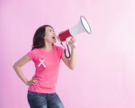 Gelukkige vrouwelijke microfoon met roze lint, ideaal voor preventie van borstkankerconcept