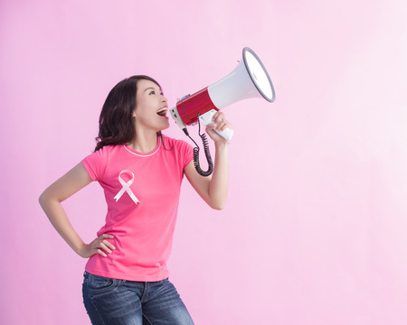 Happy woman hold microphone with pink ribbon , great for prevention breast cancer concept