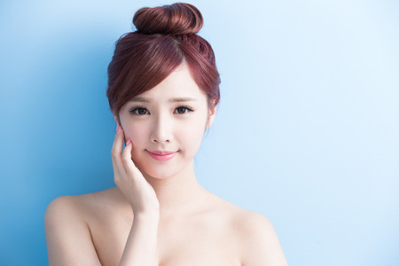 health care: beauty woman smile to you isolated on bluebackground, asian