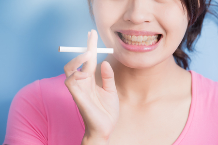unhealth: Woman holding cigarettes with yellow teeth isolated on blue background, asian