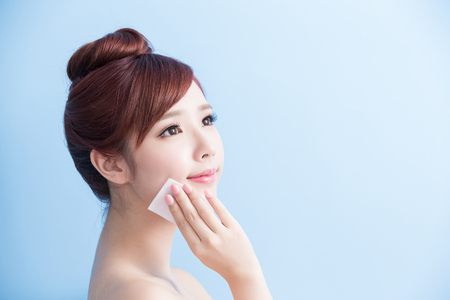 beauty skin care woman smile and make up on her face isolated on blue background, asian Stok Fotoğraf