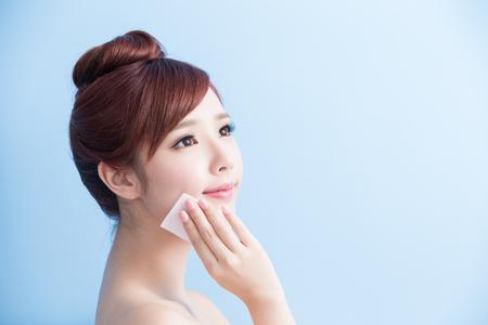 schoonheid huidverzorging vrouw glimlach en make-up op haar gezicht geïsoleerd op een blauwe achtergrond, aziatisch