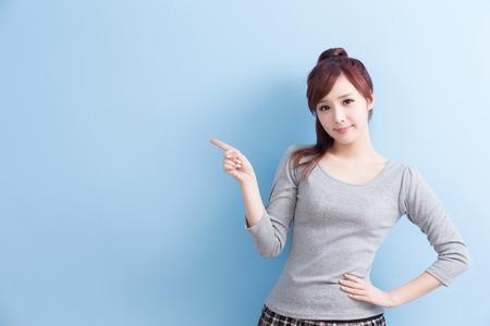 schoonheid meisje student laten zien iets en glimlach aan u met geïsoleerde op blauwe achtergrond, aziatisch