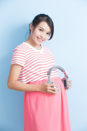 pregnant woman take earphone and smile isolated on bluebackground, asian