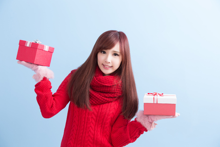 beauty woamn take gift and smile to you in christmas isolated on blue background, asian 版權商用圖片