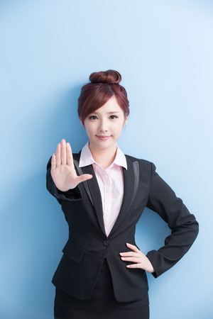 woman stop: business woman do a stop gesture with isolated on blue background, asian
