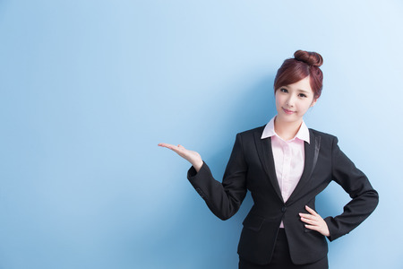 business woman is smile and show something to you with isolated on blue background, asian