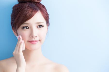 美容皮膚のケア女性の笑顔とアジアの青い背景に分離された彼女の顔を構成します。